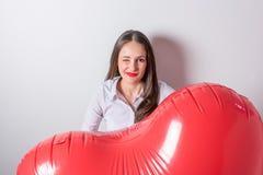 Jonge mooie vrouw die een hart gevormde luchtballon houden De dagconcept van de valentijnskaart ` s stock fotografie