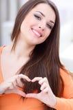 Jonge mooie vrouw die een hart maakt ondertekenen Stock Afbeeldingen
