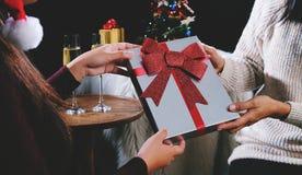 Jonge mooie vrouw die een heden geven aan vriend Kerstmis of nieuw Stock Foto