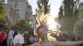 Jonge mooie vrouw die en op straat tijdens festival, het glimlachen die, mensen toejuichen springen, zon die helder glanzen rondw stock video