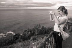 Jonge mooie vrouw die foto's van prachtig zeegezicht op Atlantische kustlijnklip nemen in zwart-wit Royalty-vrije Stock Fotografie