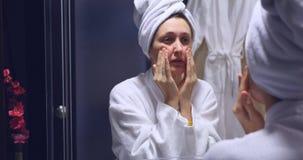 Jonge mooie vrouw die gezichtsmassage in de badkamers maken stock video
