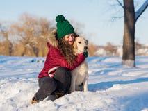 Jonge mooie vrouw die golden retrieverhond koesteren Stock Foto