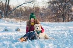 Jonge mooie vrouw die golden retrieverhond in sneeuw koesteren Stock Fotografie