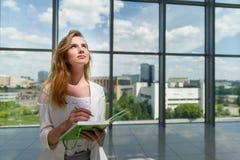 Jonge mooie vrouw die groen notitieboekje houden Stock Fotografie
