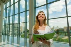Jonge mooie vrouw die groen notitieboekje houden Stock Afbeelding