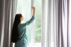 Jonge mooie vrouw die groot venster openen royalty-vrije stock afbeelding