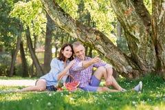 Jonge, mooie vrouw die haar echtgenoot omhelzen terwijl hij ergens richt Royalty-vrije Stock Foto's