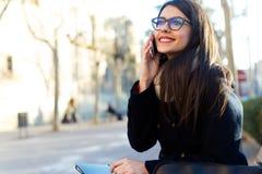 Jonge mooie vrouw die haar mobiele telefoon in de straat met behulp van Royalty-vrije Stock Foto