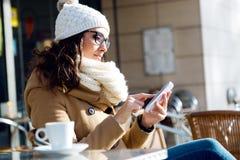 Jonge mooie vrouw die haar mobiele telefoon in een koffie met behulp van Royalty-vrije Stock Afbeelding