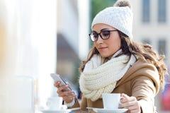 Jonge mooie vrouw die haar mobiele telefoon in een koffie met behulp van Stock Fotografie