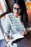 Jonge mooie vrouw die haar mobiele telefoon in koffie met behulp van Royalty-vrije Stock Afbeelding