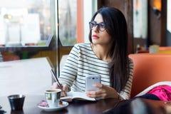 Jonge mooie vrouw die haar mobiele telefoon in koffie met behulp van Stock Afbeeldingen