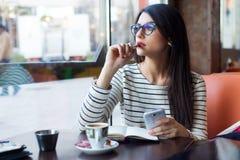 Jonge mooie vrouw die haar mobiele telefoon in koffie met behulp van Royalty-vrije Stock Foto