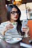 Jonge mooie vrouw die haar mobiele telefoon in koffie met behulp van Royalty-vrije Stock Fotografie