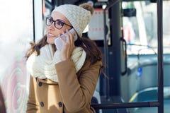 Jonge mooie vrouw die haar mobiele telefoon op een bus met behulp van Stock Fotografie