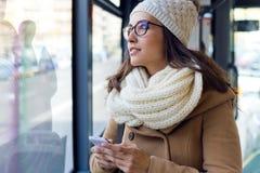 Jonge mooie vrouw die haar mobiele telefoon op een bus met behulp van Royalty-vrije Stock Foto