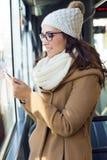 Jonge mooie vrouw die haar mobiele telefoon op een bus met behulp van Royalty-vrije Stock Afbeeldingen