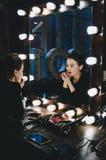 Jonge mooie vrouw die haar samenstellingslippen toepassen, bekijkend in een spiegel, die op stoel zitten Theaterkleedkamer met Royalty-vrije Stock Foto's