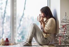 Jonge mooie vrouw die hete koffiezitting op venstervensterbank drinken Stock Afbeeldingen
