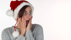 Jonge mooie vrouw die in Kerstmishoed verrast of geschokt kijken stock footage