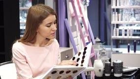 Jonge mooie vrouw die kleurstof voor haar haar kiezen bij de schoonheidssalon royalty-vrije stock fotografie