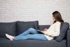 Jonge mooie vrouw die laptop computer met behulp van die gelukkig lettend op en doorbladerend of doend online Internet thuis mode Royalty-vrije Stock Foto's