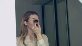 Jonge mooie vrouw die make-up met borstel voor de spiegel toepassen stock footage