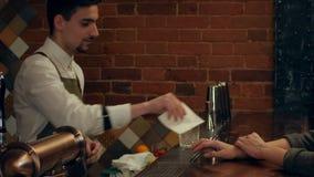 Jonge mooie vrouw die met de barman spreken, en op haar cocktail in bar lachen wachten stock footage
