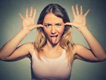 Jonge mooie vrouw die met grappig gezicht iemand bespotten die haar tong uit plakken royalty-vrije stock fotografie