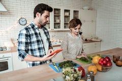 Jonge mooie vrouw die met grote oorringen greens in de keuken snijden stock afbeeldingen