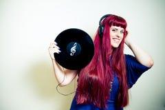 Jonge mooie vrouw die met hoofdtelefoons en vinylverslag dansen Stock Foto's