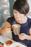 Jonge mooie vrouw die met kort haar stomend koffie drinken stock afbeelding