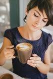 Jonge mooie vrouw die met kort haar stomend koffie drinken royalty-vrije stock afbeelding