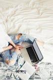 Jonge mooie vrouw die met laptop aan het bed werken Stock Fotografie
