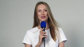 Jonge mooie vrouw die met microfoon spreken stock video