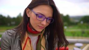 Jonge mooie vrouw die met oogglazen een boekzitting op een bank buiten in een park in de zomer lezen Sluit omhoog van gezicht 4 stock video