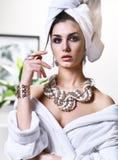 Jonge mooie vrouw die met witte handdoek op hoofd de spiegel bekijken die badjas en gouden pareljuwelen dragen Royalty-vrije Stock Afbeelding