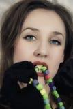 Jonge mooie vrouw die multi-coloured parels bijt Royalty-vrije Stock Foto's