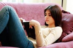 Jonge mooie vrouw die op de bank liggen en boek lezen Royalty-vrije Stock Afbeeldingen