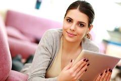 Jonge mooie vrouw die op de laag liggen en tabletcomputer houden Stock Fotografie