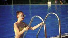 Jonge mooie vrouw die op de ladder in zwembad beklimmen zonlicht stock video