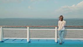 Jonge mooie vrouw die op dek van cruiseschip lopen en bij mening genieten van stock footage
