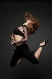 Jonge mooie vrouw die op een zwarte springt Royalty-vrije Stock Fotografie