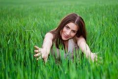 Jonge mooie vrouw die op groen gebied glimlachen royalty-vrije stock foto