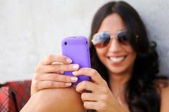 Jonge mooie vrouw die op telefoon schrijft Royalty-vrije Stock Afbeeldingen
