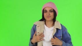 Jonge mooie vrouw die op warm jasje zetten die aan de camera glimlachen stock footage