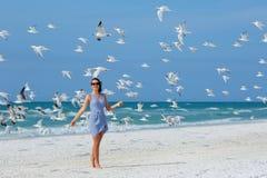 Jonge mooie vrouw die op zeemeeuwen het vliegen letten Royalty-vrije Stock Afbeeldingen
