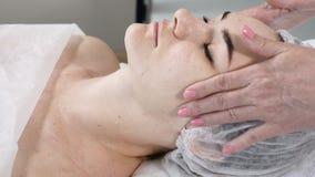 Jonge mooie vrouw die procedures in schoonheidssalon krijgen Jong mooi donkerharige die op laag liggen cosmetologist stock footage