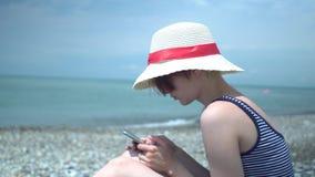 Jonge mooie vrouw die retro hoed en zwempak met blauwe en witte strepen in eenzaam de zomerstrand dragen die smartphone gebruiken stock videobeelden
